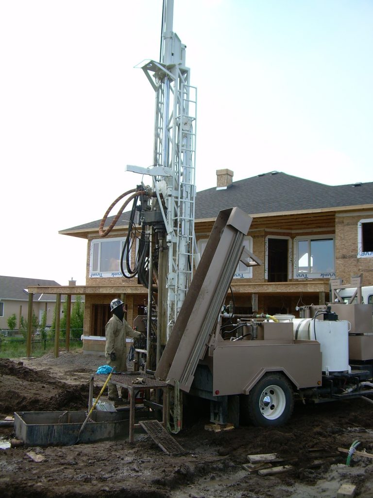 Drilling for vertical loop geothermal project - new home in West Lethbridge